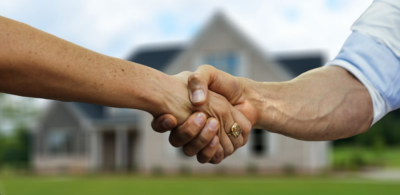 Real estate agent shaking hands with buyer in front of house